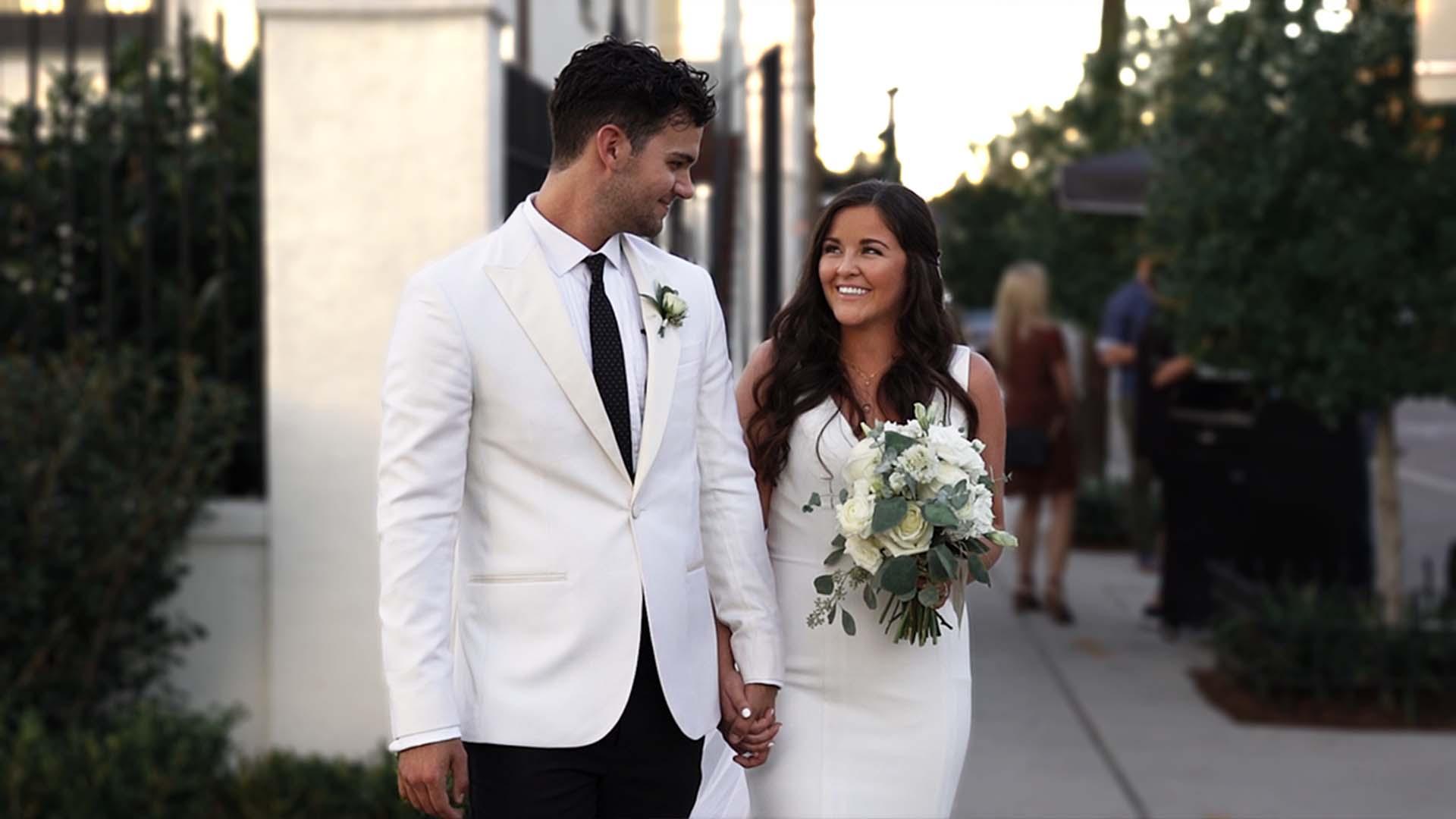 Bride and Groom Walking Down Sidewalk Next To Il Mercato Wedding Venue